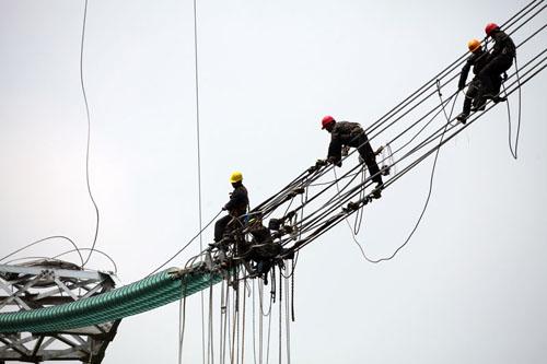 送变电公司电力建设者在浙江丽水段线路工程杆塔上进行平衡挂线施工